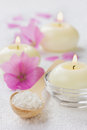 Spa composition with sea salt bath in wooden spoon pink flowers and burning candles on a white surface aromatherapy concept space Stock Photo