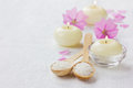 Spa composition with sea salt bath in wooden spoon pink flowers and burning candles on a white surface aromatherapy concept space Royalty Free Stock Photo