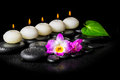 Spa concept of orchid flower, green leaf and row white candles o Royalty Free Stock Photo