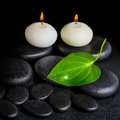 Spa concept of two white candles and green leaf on black zen sto Royalty Free Stock Photo