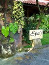 Spa direction sign bali resort a photograph showing the beautiful garden of a tropical hotel in indonesia with a stone directing Stock Photos