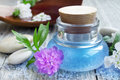 Spa essence bottle flowers and sea salt oil with massage stones Stock Photo