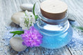 Spa essence bottle flowers and sea salt oil with massage stones Royalty Free Stock Images