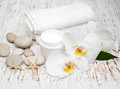 Spa essentials cream white towels and orchids Royalty Free Stock Photo
