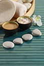 Spa essentials orchid massage stones towel pumice and ointments on green slatted wooden surface Stock Photography