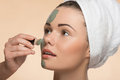 Spa girl with a  towel on her head applying facial Royalty Free Stock Photo