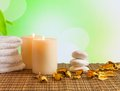 Spa massage border background with towel stacked candles and perfumed leaves on bamboo table Royalty Free Stock Photo