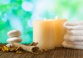 Spa massage border background with towel stacked candles and perfumed leaves on green bokeh Stock Image