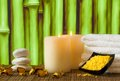 Spa massage border background with towel stacked candles and sea salt on bamboo Royalty Free Stock Image