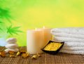 Spa massage border background with towel stacked candles and sea salt on bamboo table Stock Photography