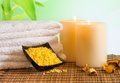 Spa massage border background with towel stacked candles and sea salt on bamboo table Royalty Free Stock Photos