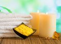 Spa massage border background with towel stacked candles and sea salt on green bokeh Royalty Free Stock Images