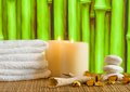 Spa massage border background with towel stacked, candles and stone Royalty Free Stock Photo