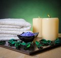 Spa massage border background with towel stacked perfumed leaves candle and sea salt on green gradient Stock Images