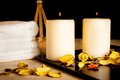 Spa massage border background with towel stacked perfumed leaves and candles on black Stock Images
