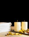 Spa massage border background with towel stacked perfumed leaves and candles on black Royalty Free Stock Image