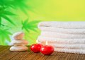 Spa massage border background with towel stacked red candles and stone on green Royalty Free Stock Image
