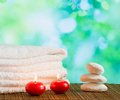 Spa massage border background with towel stacked red candles and stone on green bokeh Royalty Free Stock Photo