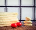 Spa massage border background with towel stacked stone and red candles warm atmosphere Royalty Free Stock Photo