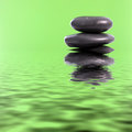 Spa massage stones in green water fresh conceptual background with copyspace of a stack of smooth black basalt with reflections Royalty Free Stock Photo