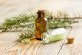 Spa with organic spruce oil and sea salt in glass bottles on wooden table background