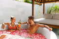 Spa Relax. Couple In Love In Flower Bath Drinking Drinks Royalty Free Stock Photo