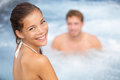 Spa resort jacuzzi hot tub couple woman and man women girl enjoying water in outdoor whirlpool smiling happy at camera during Royalty Free Stock Photography