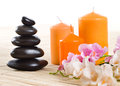 Spa still life of black stone and orange candle on white background isolated Stock Images