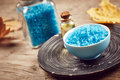 Spa still life with blue sea salt and autumn leaves on wooden background Royalty Free Stock Photo