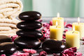 Spa still life with hot stones and candles focus on stack of Royalty Free Stock Photo