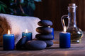 Spa still life with hot stones essential oil and candles dark tone Royalty Free Stock Photo