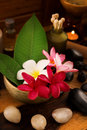 Spa still life setting aromatic candles frangipani flower cold hot stones Royalty Free Stock Photos