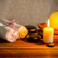 Spa still life of white towels candle thai herbal compress bal balls in basket and zen basalt stones on wooden background closeup Royalty Free Stock Photography