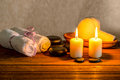 Spa still life of white towels candles thai herbal compress ba balls in basket and zen basalt stones on wooden background closeup Stock Image