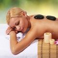 Spa Stone Massage. Beautiful Blonde Woman Royalty Free Stock Photo
