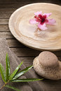 Spa treatment a wood bowl filled with water and a flower on wood background with bamboo and stones Royalty Free Stock Image