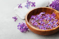 Spa and wellness composition with perfumed lilac flowers water in wooden bowl and terry towel on stone background aromatherapy Royalty Free Stock Photo