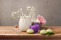 Spa and wellness concept with flowers in vase and candles on wooden table Royalty Free Stock Photo