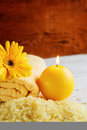 Spa yellow products setting. Sea salt ,towel and candles on dark wooden background Royalty Free Stock Photo