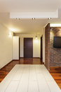 Spacious apartment corridor and brown wooden door Stock Images