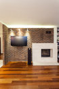 Spacious apartment fireplace brick wall with and tv Royalty Free Stock Photos