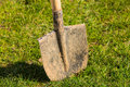 Spade in the ground stuck with fresh green grass Royalty Free Stock Image