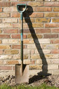 Spade leaning against Old Garden Wall Royalty Free Stock Image