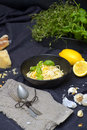 Spaghetti al limone bowl of surrounded by lemons parmesan pieces cloth with spoon and fork plus garlic and herbs Stock Photo