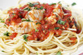 Spaghetti all arrabbiata with fish side view garnished parsley seen closeup form the the sauce is made from tomato garlic olive Royalty Free Stock Photo