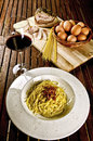 Spaghetti alla carbonara italian traditional recipe with ingredients on background and a glass of red wine Stock Image