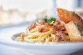 Spaghetti with bacon and garlic bread Royalty Free Stock Photo