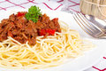 Spaghetti bolognese dinner on red and white checkered tablecloth with chianti bottle and wine glass just showing in the background Stock Photography