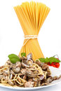 Spaghetti with clams and plate raw bunch in the background over white Royalty Free Stock Image