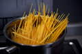 Spaghetti from durum wheat are cooked in a metal pot on the fire Royalty Free Stock Photo